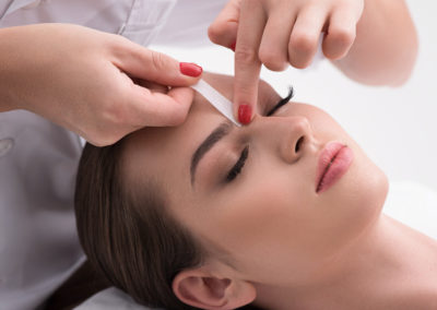 Young woman tweezing her eyebrows in beauty saloon